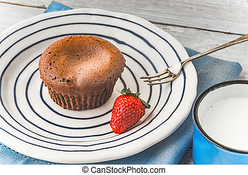 Chocolate fondant on the ceramic plate with strawberry and milk