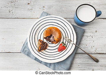 Chocolate fondant on the ceramic plate with strawberry and milk top view
