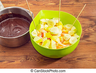 Chocolate fondue on an old rustic wooden table
