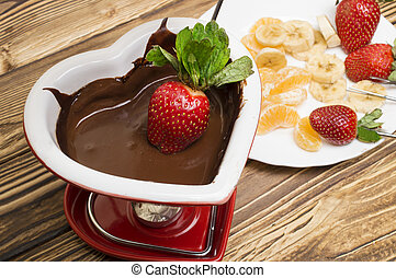 Chocolate fondue with strawberries and fruits served in a restaurant. Valentine's Day