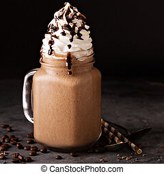 Chocolate frappe coffee with whipped cream and syrup on dark...