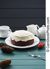 Chocolate fruit cake with cream cheese and black tea decorated with cones on dark background