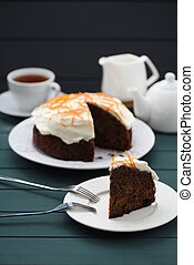 Chocolate fruit cake with cream cheese glasing and orange peel served with black tea on dark background
