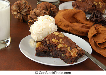 Chocolate fudge brownies with nuts and vanilla ice cream