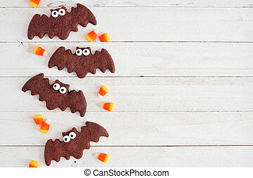 Chocolate Halloween bat cookie side border. Overhead view on a white wood background.