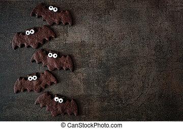 Chocolate Halloween bat cookie side border. Top view over a dark background.