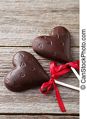 Chocolate hearts on grey wooden background