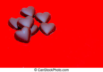 Chocolate hearts on red
