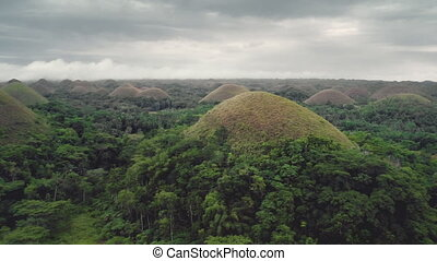 Chocolate Hills aerial view: mountains with high trees and rain clouds on spring day. Picturesque natural wonder of Bohol Island, Philippines, Visayas archipelago. Magnificent footage shot in 4K, UHD