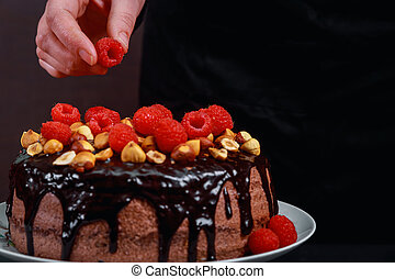 Chocolate homemade cake decorated with raspberries by male hands on a gray background.