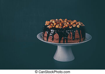 Chocolate homemade cake decorated with raspberries on a gray background.