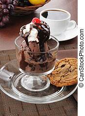 A dish of ice cream with a chocolate chip cookie and whipped cream