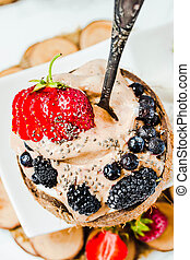 Chocolate ice cream with berries on coconut cup. Summer food and healthy dessert concept.