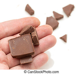 chocolate in his hand on a white background