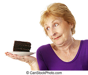 Fit senior woman making food choices. She is unable to resist the chocolate cake. Isolated on white.