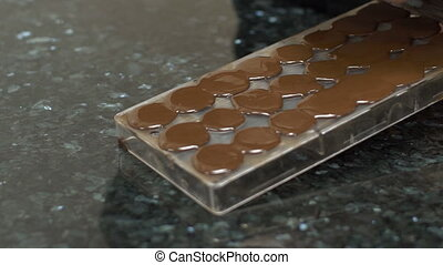 Chocolate is being deleted from baking dish with spatula,...