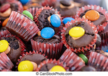 Chocolate little cupcakes along with candy is a street food in local market in Thailand, closeup. Thai sweet food