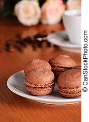 Two chocolate macaroons on pink striped background
