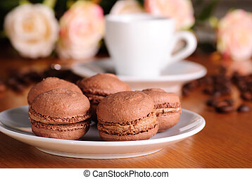 Two chocolate macaroons on wooden table with coffee background
