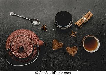 Chocolate marshmallows hearts with spices on black desk .Cinnamon, star anise, teapot