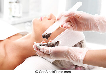 Chocolate mask. - Beautician mask is applied to the woman's...