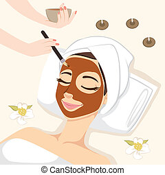 Woman having chocolate mask treatment therapy lying down on massage bed with flowers and perfumed candles