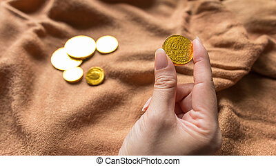Chocolate money, Chocolate gold coins in woman hands as a...