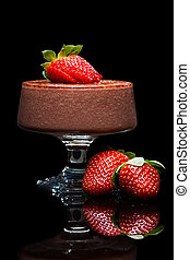 Chocolate mousse dessert with delicious red strawberries. Isolated on black.