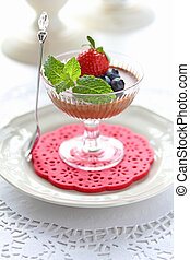 Chocolate Mousse dessert in a glass with strawberry, blueberry and mint