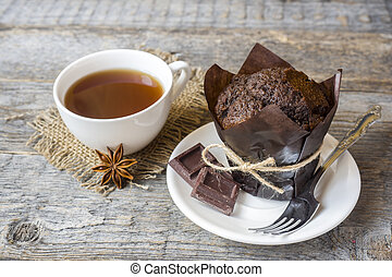 Chocolate muffin and a Cup of coffee on a wooden background.
