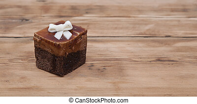 Chocolate muffin with white ribbon on wooden background