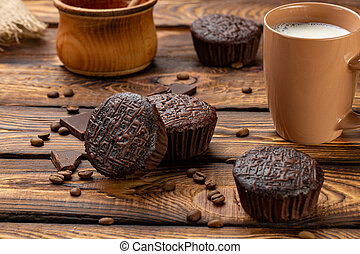 Chocolate muffins on a broun rustic wooden table - selective...