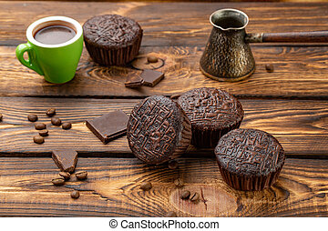 Chocolate muffins on broun wooden background - The Chocolate...