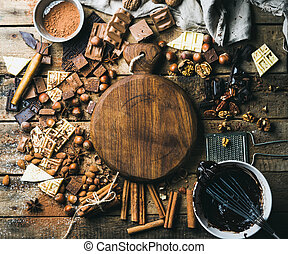 Chocolate, nuts, cocoa powder, spices with wooden board in center