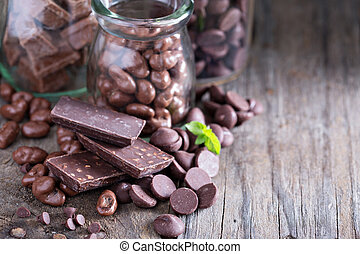 Chocolate pieces, chips, candies and bars in jars