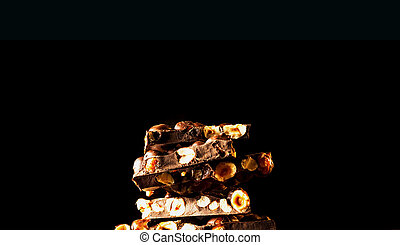 Chocolate pieces with almonds on dark background. Copy space