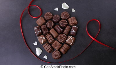 Chocolate pralines heart shaped on black background. Valentines day concept. Loving chocolate and sweets concept. Dolly shot