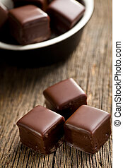 chocolate pralines on wooden background