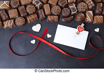 Chocolate pralines with card Valentines day on black background
