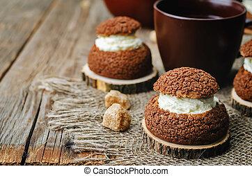 chocolate profiteroles, Shu, with cream on a dark wood ...