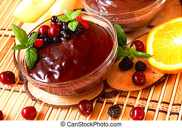Chocolate pudding with berries and mint - bowls of chocolate...