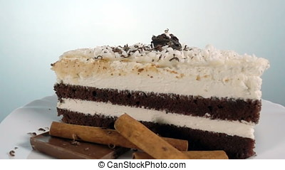 Chocolate shaving falling on a slice of cake, slow motion at...