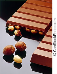 Chocolate bars with hazelnut on dark reflective background