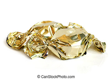 Chocolate sweets in golden foil on a white background