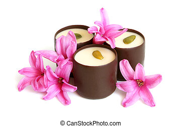 Chocolate sweets with pink flowers of hyacinth on a white...