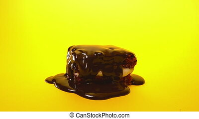 Chocolate topping glaze pouring on biscuit cake dessert on...