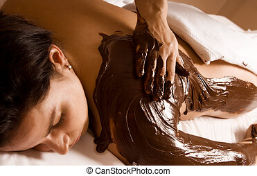 Chocolate treatment - young woman getting a chocolate...