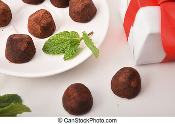 Chocolate truffles on white table with gift. Top elevated  view. Horizontal composition.