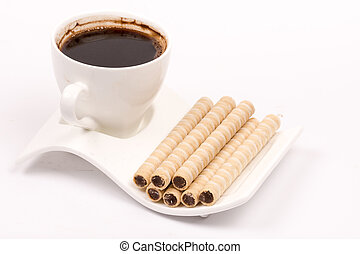 Chocolate wafer cream rolls and white cup of black coffee