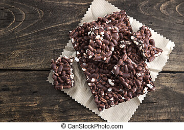 chocolate with puffed rice bar on wooden table, from above